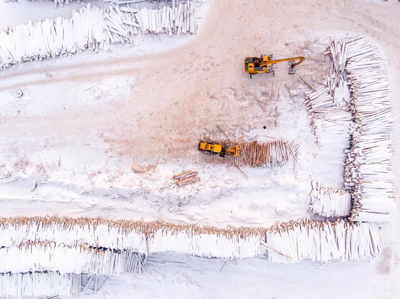 De ladertractor pakt logboekenhout het oogsten, Zaagmolen in Hoogste meningsantenne royalty-vrije stock afbeeldingen