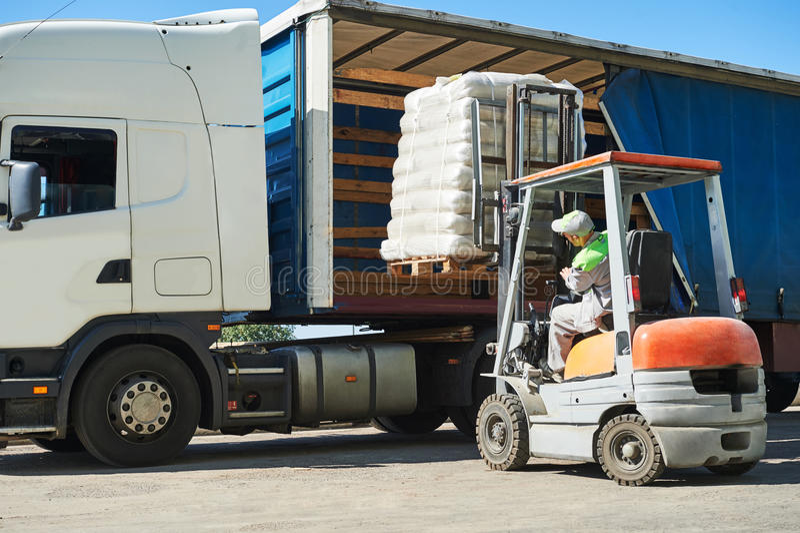 De ladingswerken Vorkheftruck met lading en vrachtwagenvrachtwagen royalty-vrije stock fotografie
