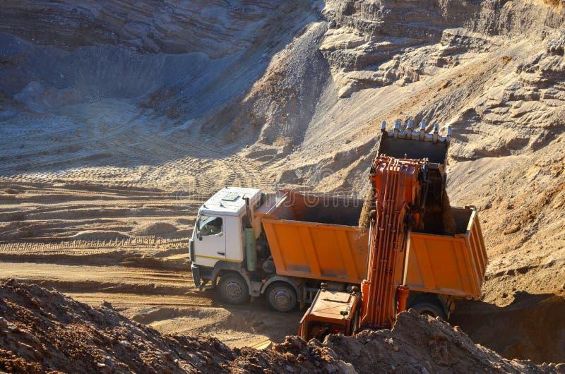 De ladingszand van de graafwerktuigemmer in het lichaam van een zware stortplaatsvrachtwagen royalty-vrije stock foto's