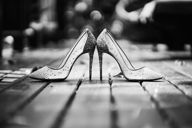 De lage hoek van hoge hielen schittert de plaats van vrouwenschoenen op de houten vloer in zwart-wit stock afbeelding