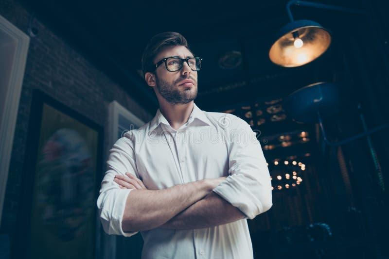 De lage hoekfoto van een zekere succesvolle jonge donkerbruine werkgever met varkenshaar, in glazen, kleedde zich goed Zo modieus stock afbeelding