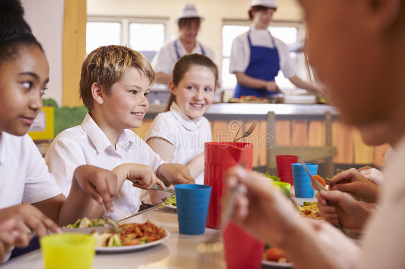 De lage schooljonge geitjes bij een lijst in schoolcafetaria, sluiten omhoog royalty-vrije stock afbeeldingen