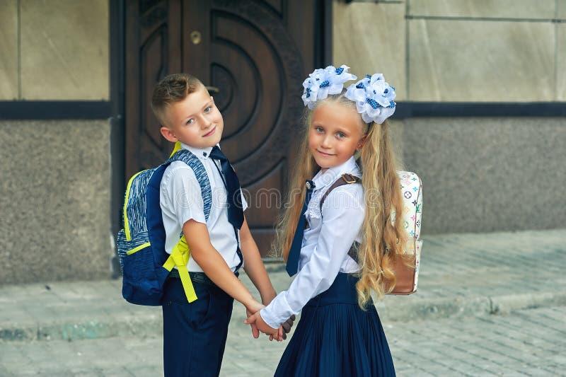 De lage schoolstudenten gaan naar school voor klassen De eerste dag van de herfst royalty-vrije stock afbeeldingen