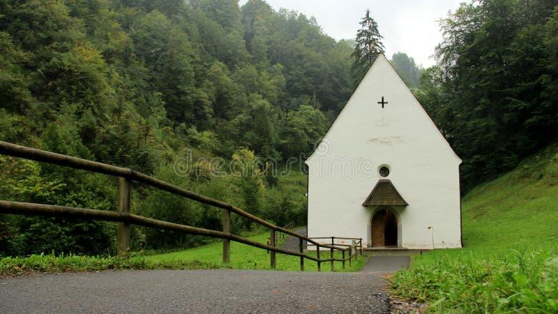 De Lagere Kapel van Flueliranft met Motregen en Houten omheiningen stock afbeeldingen