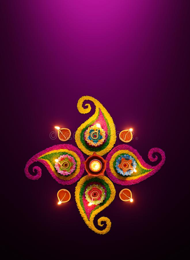 De lampen van de Diyaolie op kleurrijke rangoli worden aangestoken die royalty-vrije stock afbeeldingen