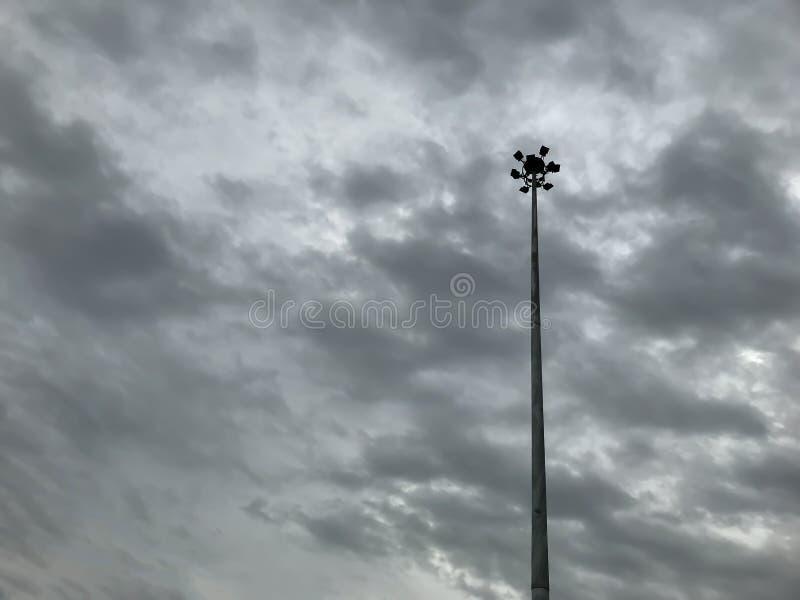 De de lamppost of straatlantaarn met regen betrekt komst in hemel vóór onweer voor achtergrond stock afbeelding