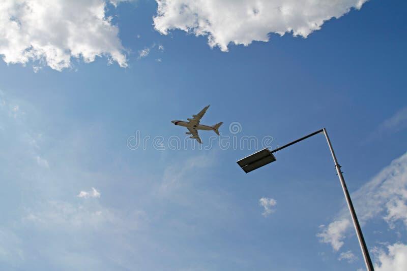 De lamppost van het straatmetaal op blauwe hemelachtergrond met vliegtuig en wolken in Skolkovo stock foto