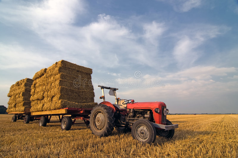 De landbouw rode tractor van de Apparatuur met stro op t stock foto's