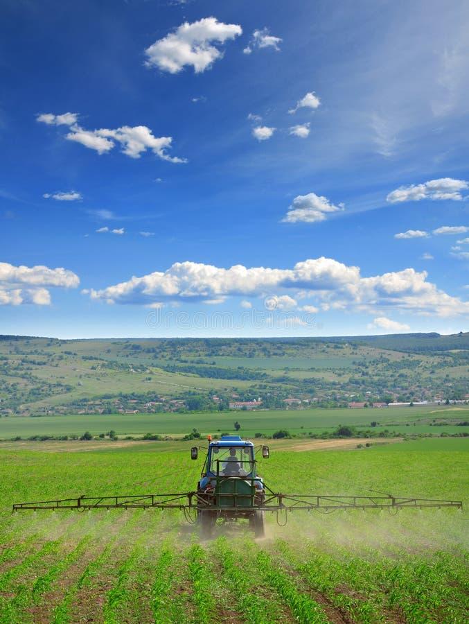 De landbouw van tractor die en op gebied ploegen bespuiten royalty-vrije stock afbeeldingen