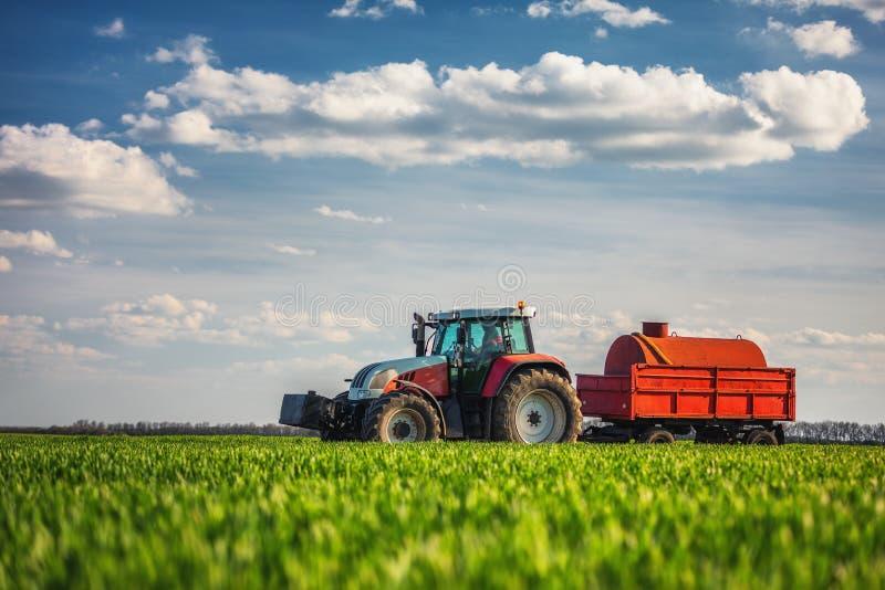 De landbouw van tractor die en op gebied ploegt bespuit stock afbeeldingen