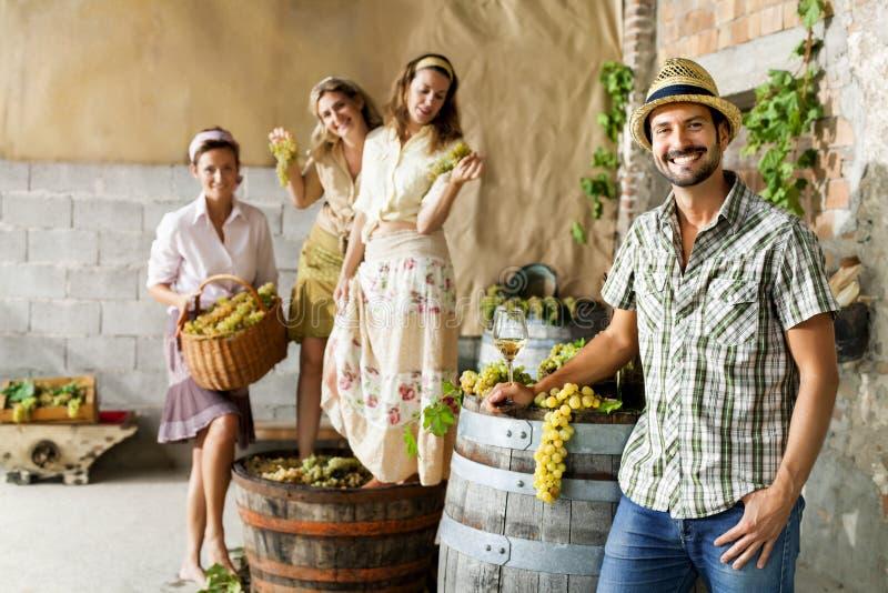 De landbouwer drinkt wijn terwijl vrouwen die druiven in een oud landbouwbedrijf verpletteren royalty-vrije stock fotografie