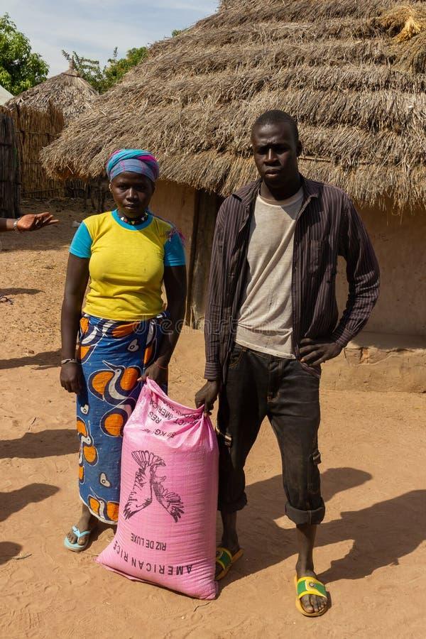 De landbouwer en de vrouw ontvangen zak rijst stock foto