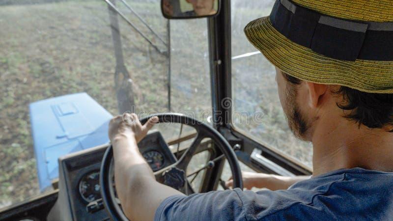 De landbouwer in hoed, zit binnen in de tractorcabine, berijdt op het gebied met ploeg stock afbeelding