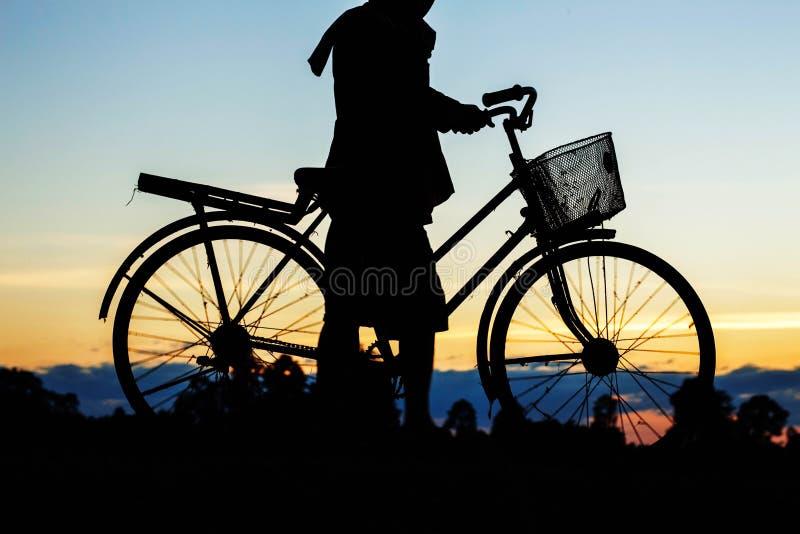 De landbouwers zijn fiets met silhouetten royalty-vrije stock foto's