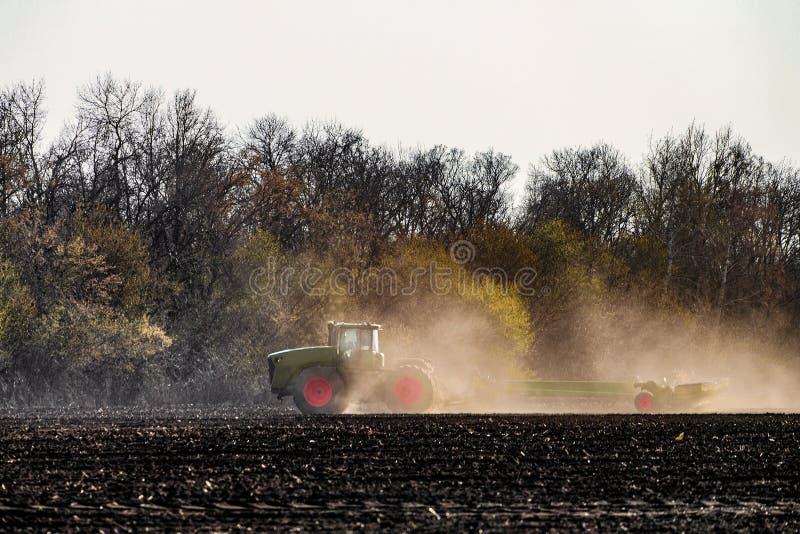 De landbouwtrekker met zaaimachine werkt op het gebied royalty-vrije stock foto's