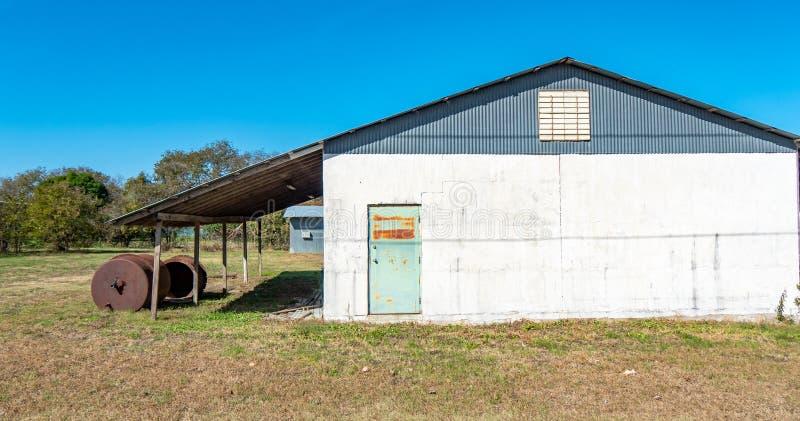 De landelijke bouw met kleurrijke, roestige deur op een grasrijk gebied, met overhangend gedeelte en roestige vloeibare tanks stock foto
