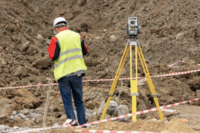 De landmeter bij de bouwwerf voert metingen uit royalty-vrije stock foto
