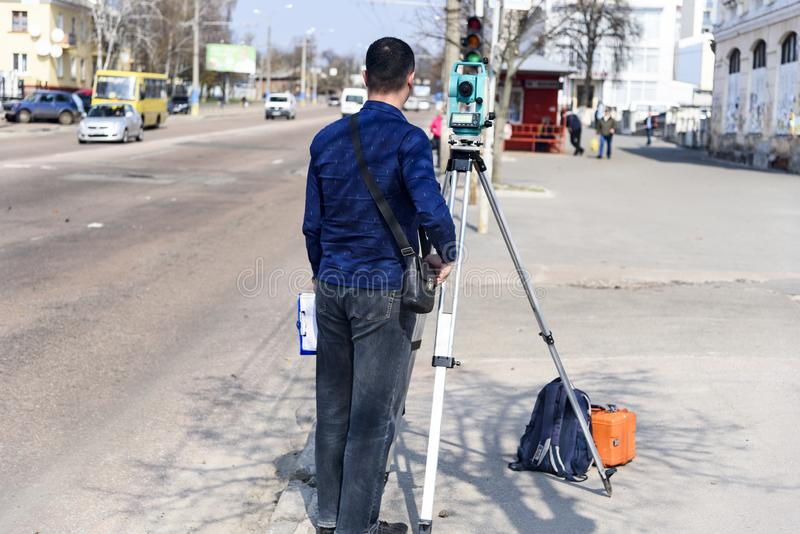 De landmeter van het ingenieursland maakt metingen op de straat van de stad van Chernigov, de Oekraïne stock foto's