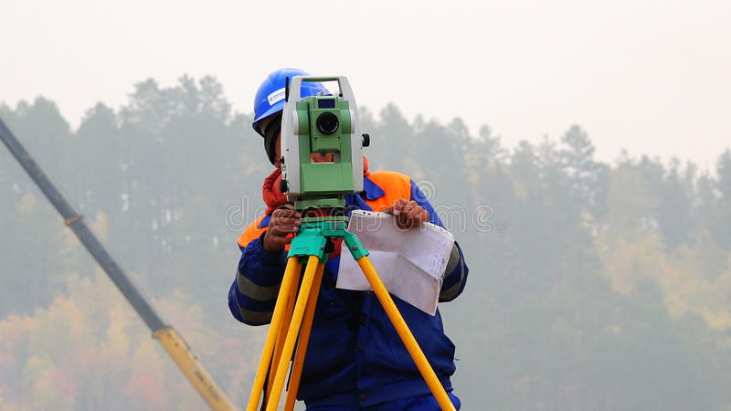 De landmeter voert het meten van verrichtingen op het niveau en de theodoliet uit stock footage