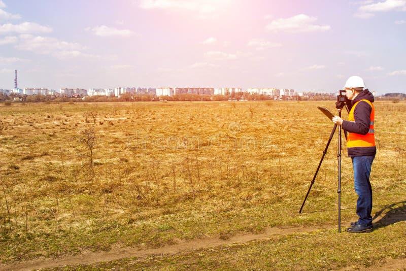 De landmetersarbeider meet de afstand en de lengte gebruikend meetapparatuur voor de bouw van een nieuw micro- district, exemplaa stock afbeelding