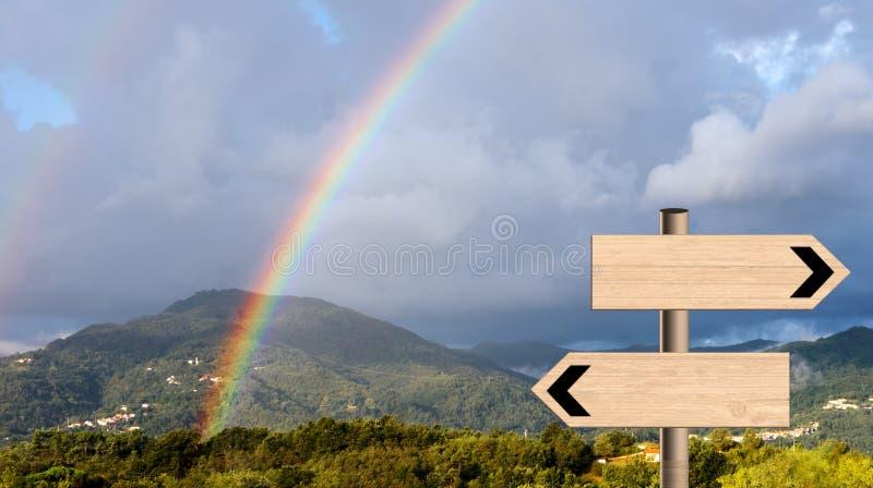 De landschapsregenboog met voorziet van wegwijzers De metafoor van de het levensrichting stock foto