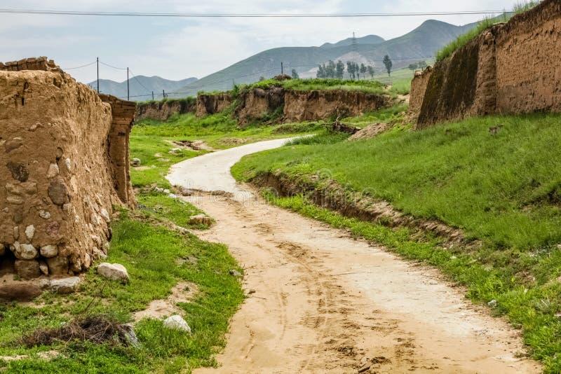 De landweg beëindigt een kleine heuvel rond een moddermuur in landelijk China met een machtslijn die over de bovenkant lopen stock foto