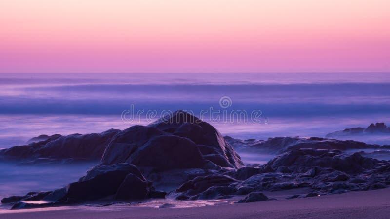 De lange blootstelling schoot bij schemer over oceaan met erachter rotsen in voorgrond en melkachtige golven stock foto