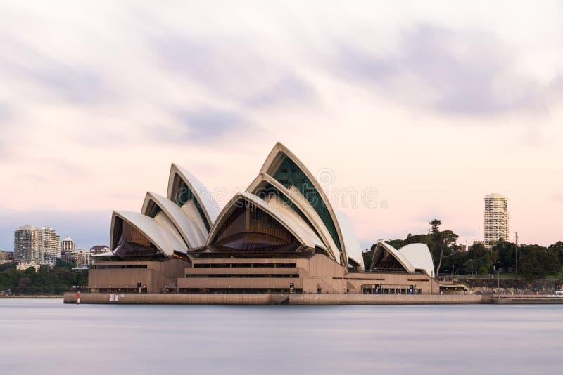 De lange blootstelling van Sydney Opera House op een bewolkte dag, haven in de voorgrond stock fotografie