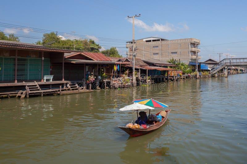 De lange boot drijft op rivier rond houten Thais oud huis royalty-vrije stock afbeeldingen