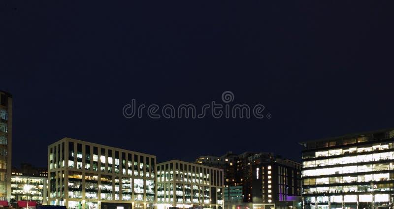 de lange cityscape mening van moderne bureauontwikkelingen stak helder bij nacht met donkerblauwe hemel geschikt voor geduurde ex stock fotografie