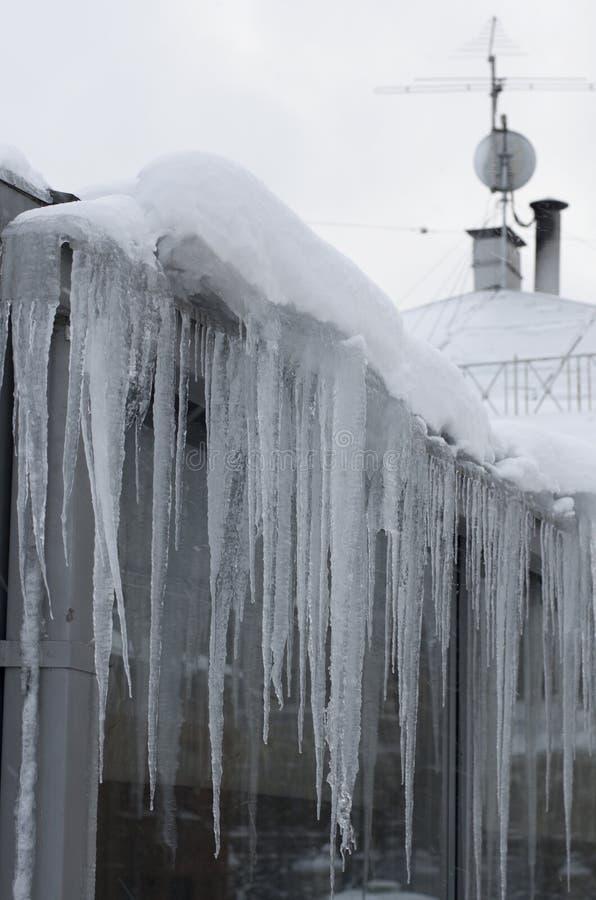 De lange ijskegels hangen van het dak van het huis stock afbeelding