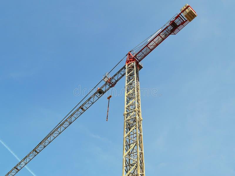De lange kraan van de bouwtoren tegen de blauwe hemel op een dag stock afbeelding