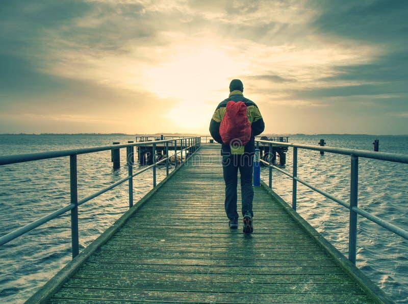 De lange mens in het warme jasje en de zwarte broek loopt op de waterkant en bekijkt het overzees De houten pijler op kust van ov royalty-vrije stock afbeelding