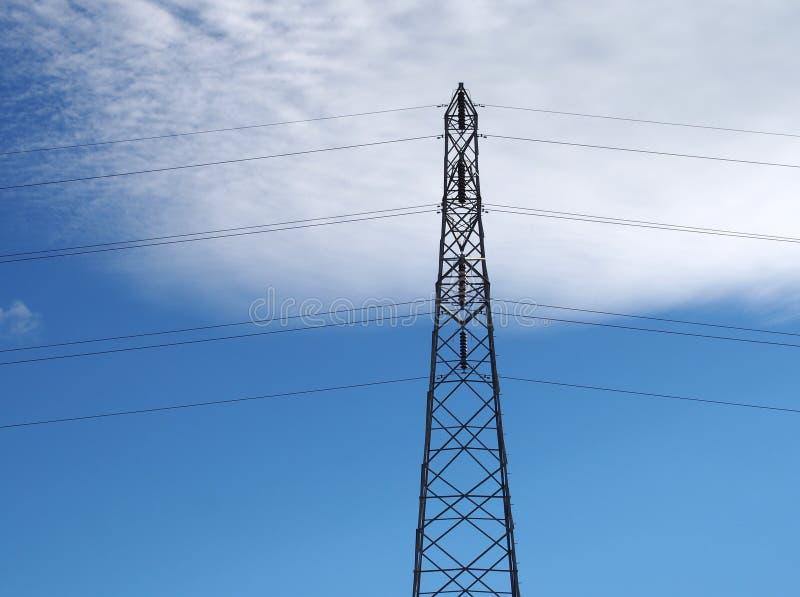 de lange pyloon van de staalelektriciteit met kabels tegen een blauwe hemel met witte wolken royalty-vrije stock afbeelding