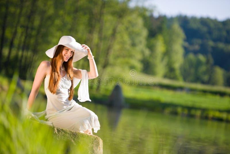 De lange rode haar romantische vrouw ontspant door meer stock foto