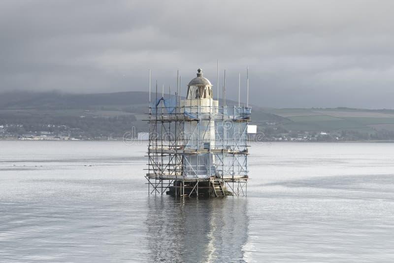 De lange toren van de vuurtorenbouw in zeewater en helder licht onder grijze hemel stock afbeelding