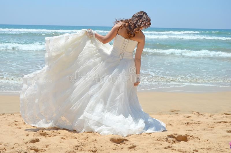 De langharige donkerbruine bruid maakt haar kleding recht die zich op het zand, het strand op de Indische Oceaan bevinden Huwelij royalty-vrije stock foto