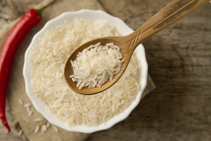 De langkorrelige rijst in een houten lepel op een achtergrond plateert, Spaanse peperpeper Het gezonde eten, dieet stock foto's