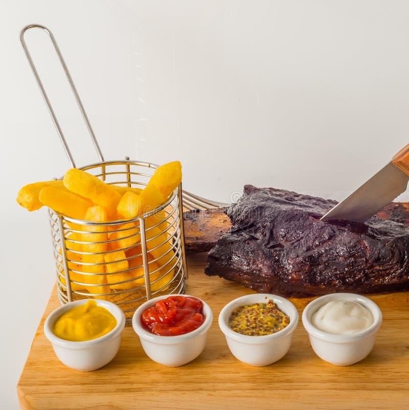 De langzame gekookte eik rookte verglaasde rundvleesrib, Frieten, saus vier stock foto