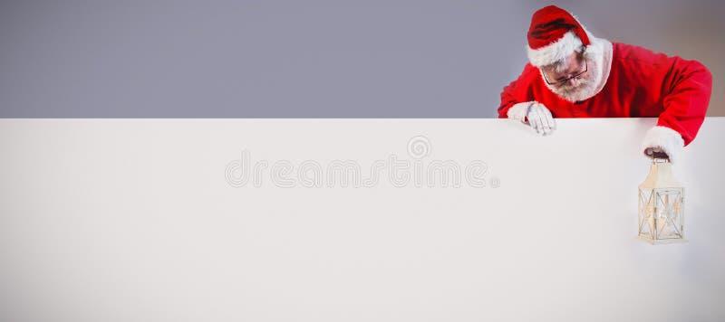 De lantaarn van de holdingskerstmis van de Kerstman op witte raad stock fotografie