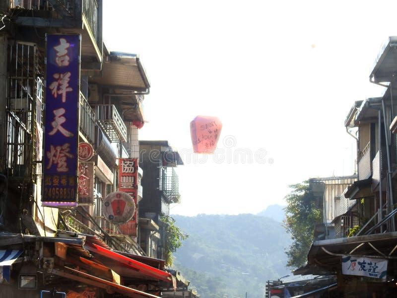 De Lantaarns die van de LChinesehemel omhoog tussen winkelhuizen vliegen stock afbeeldingen