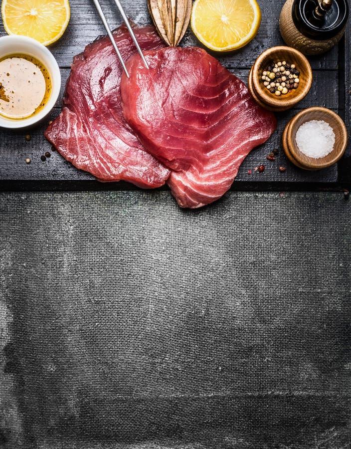 De lapjes vlees van tonijnvissen met ingrediënten voor grill of het koken op donkere uitstekende achtergrond, hoogste mening stock afbeelding