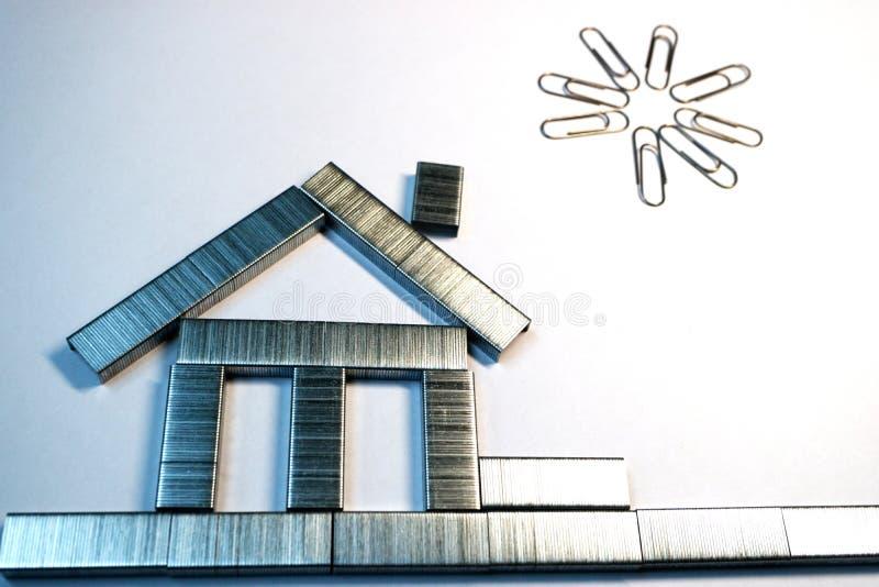 De las grapas de la grapadora se hace una casa en el Libro Blanco, sobre la casa de los clips de papel, el sol, pintura de la ofi fotografía de archivo