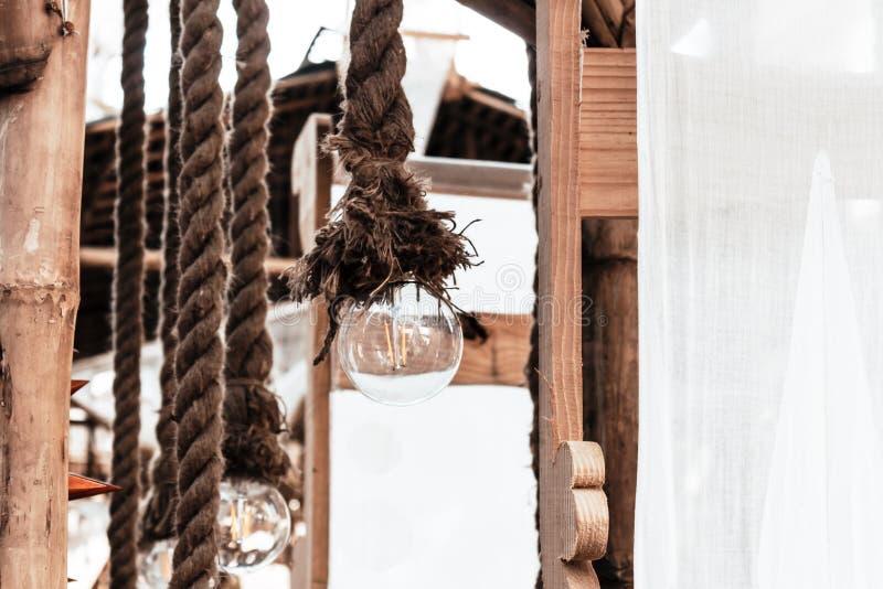 De las guirnaldas de una terraza de la playa o mirador de la luz eléctrica bulbo colgante, cuerda atada en el tejado del polo del imagenes de archivo