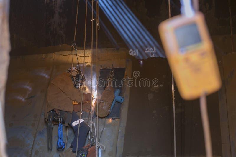 De lasser die van de kabeltoegang veiligheidsmateriaal, uitrustingshelm dragen die het hete werk doen, die in beperkte ruimte las royalty-vrije stock afbeeldingen