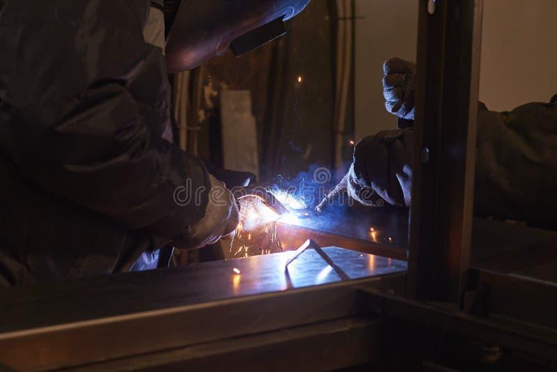 De lasser last een metaalkader voor de elektrische centrale stock afbeeldingen
