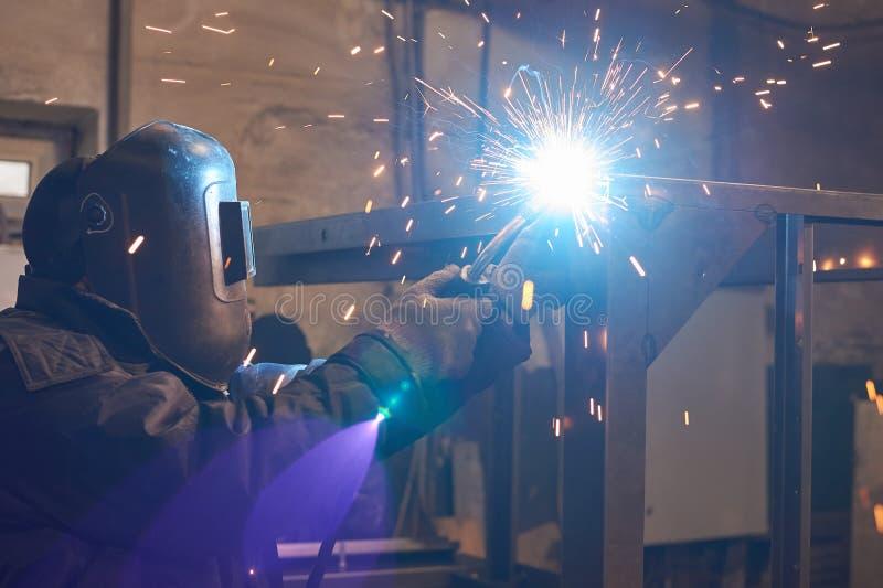 De lasser last een metaalkader voor de elektrische centrale royalty-vrije stock foto