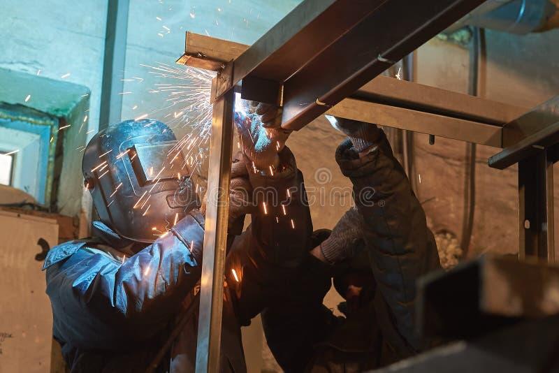 De lasser last een metaalkader voor de elektrische centrale royalty-vrije stock afbeelding