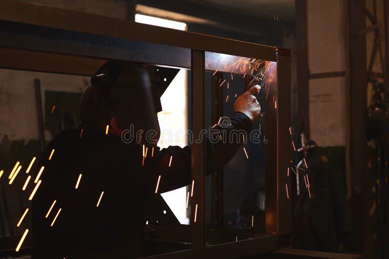 De lasser last een metaalkader voor de elektrische centrale royalty-vrije stock foto's