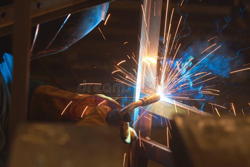 De lasser last metaaldelen, veel rook en vonken, schadelijkheid, arbeider stock afbeelding